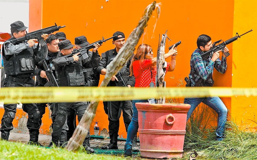 Police take aim during a shooting yesterday Jalisco.