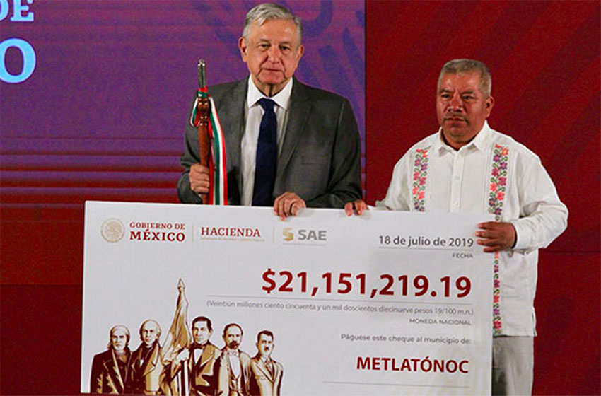 AMLO presents a check to the mayor of Metlatónoc, proceeds of an auction of narco-real estate.