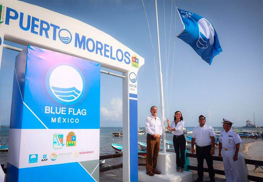Mayor raises the blue flag over a Puerto Morelos beach.
