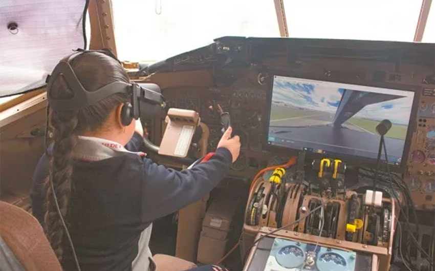 A young student flies the plane with a simulator.