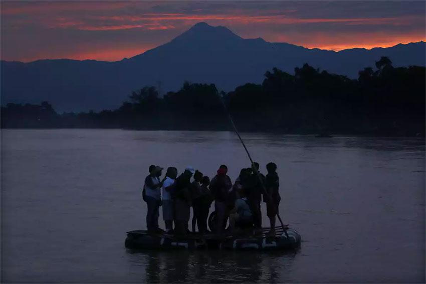 Migrants cross the Suchiate river on a raft.