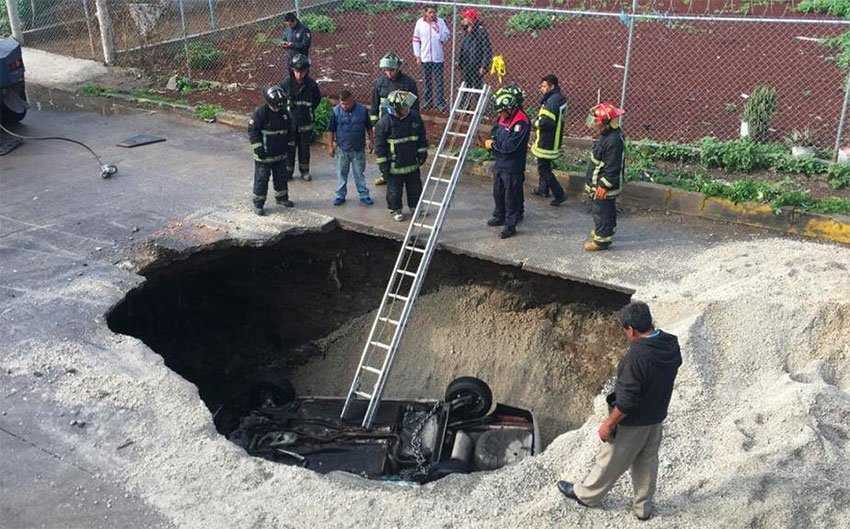 Emergency crews prepare to remove the second vehicle that fell in the large hole.