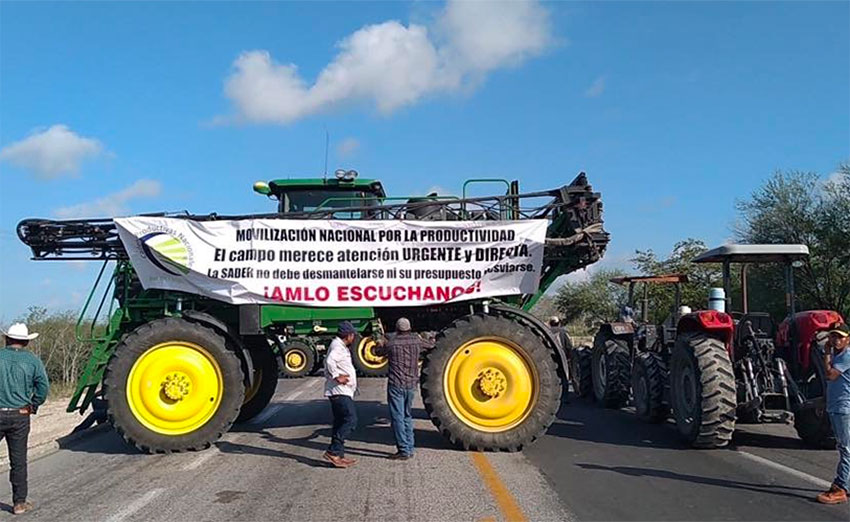 'Listen to us AMLO,' reads the sign on a farm vehicle at one of today's blockades.
