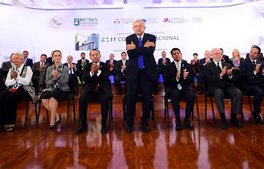 AMLO offers one of his trademark hugs at yesterday's conference.