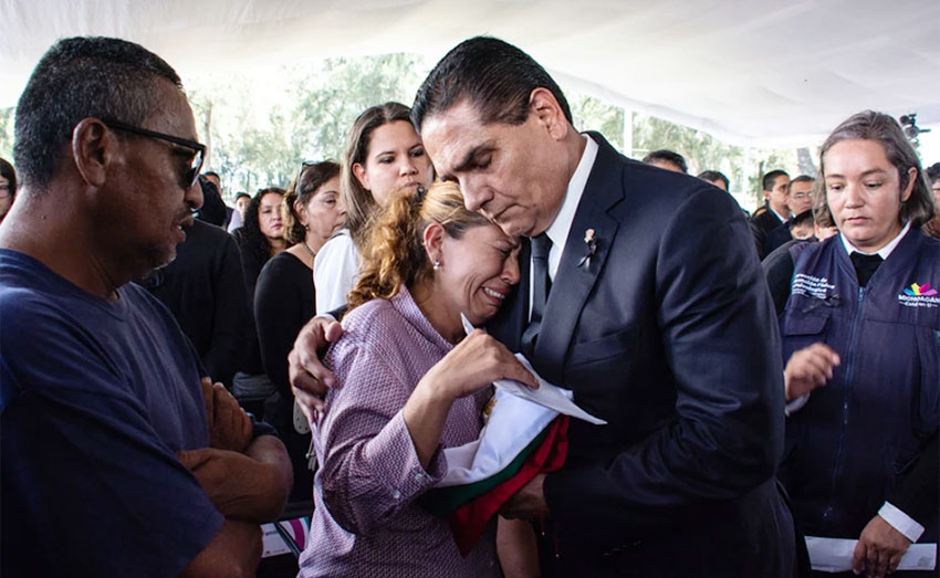 The governor comforts a survivor of a victim in Monday's attack.