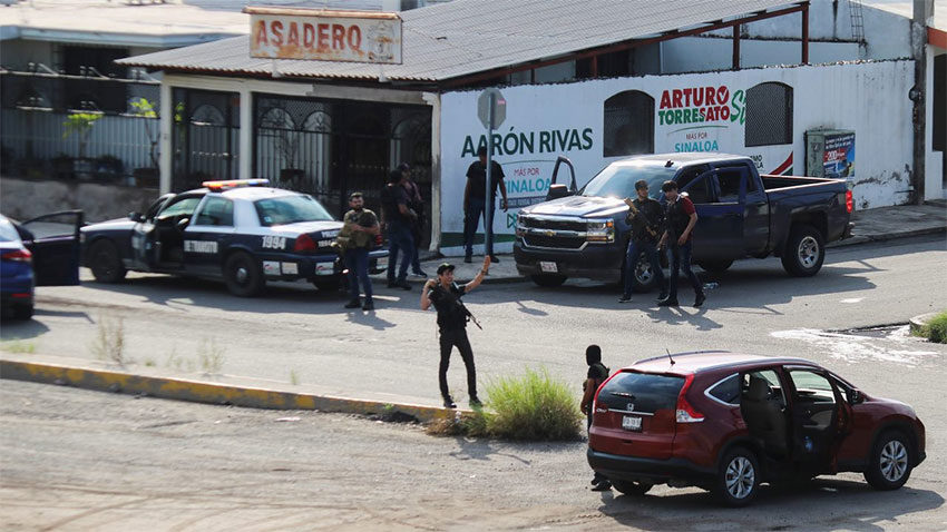 Armed civilians control a street corner in Culiacán.