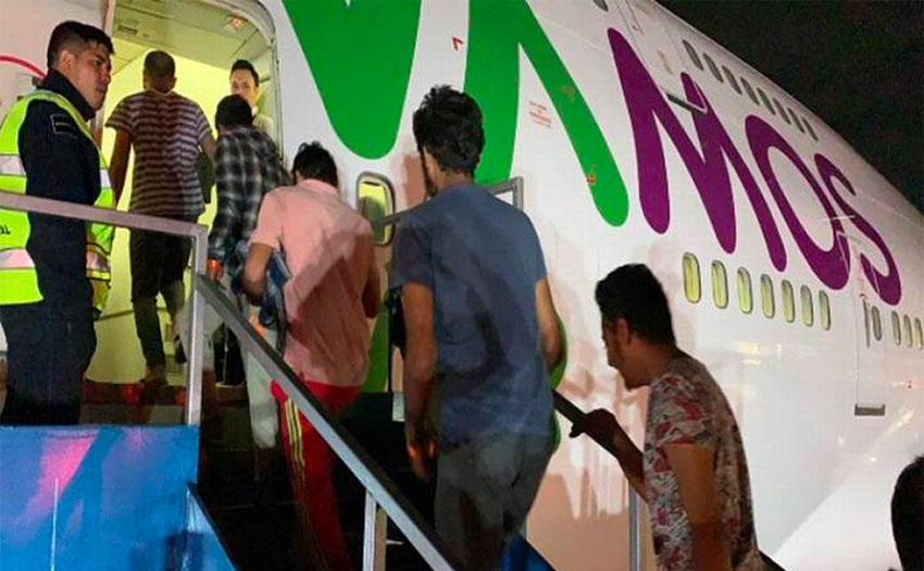 Undocumented migrants board their plane for India.