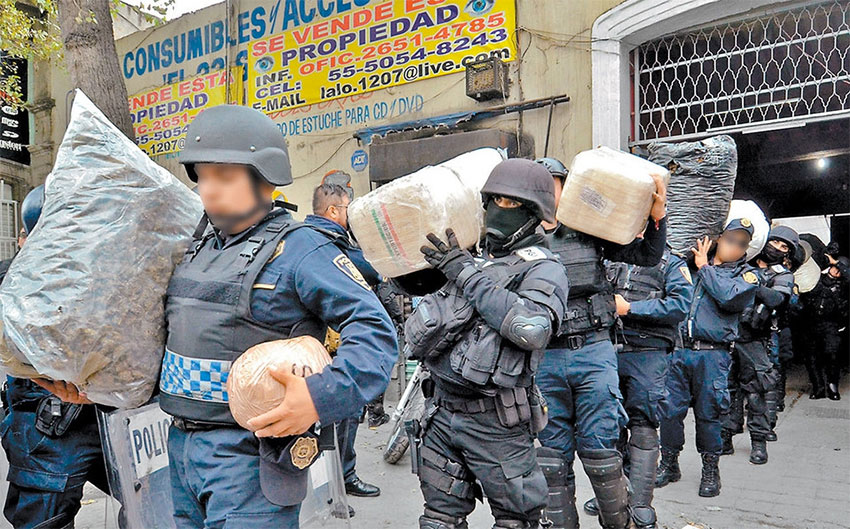 Police remove drugs from a Mexico City property after a raid on the Unión de Tepito.