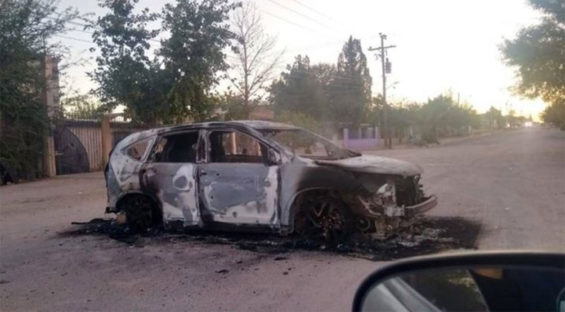 A burned-out vehicle blocks a road in Agua Prieta Monday morning.