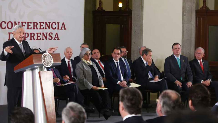 Cabinet secretaries listen as President López Obrador presents infrastructure plan.
