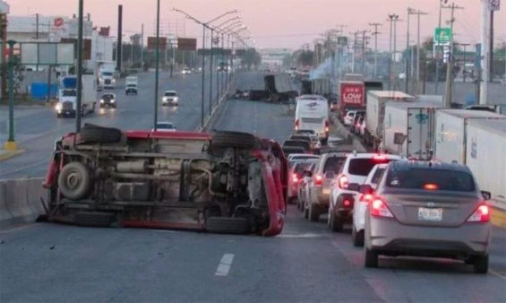 A burned vehicle blocks a highway in Nuevo Laredo Friday.