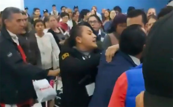 A security guard, center, breaks up a fight in Mexico City airport.