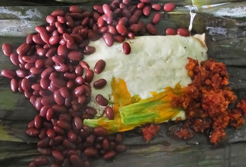 Cheese fondue on a banana leaf with pumpkin flowers, red beans and chorizo.