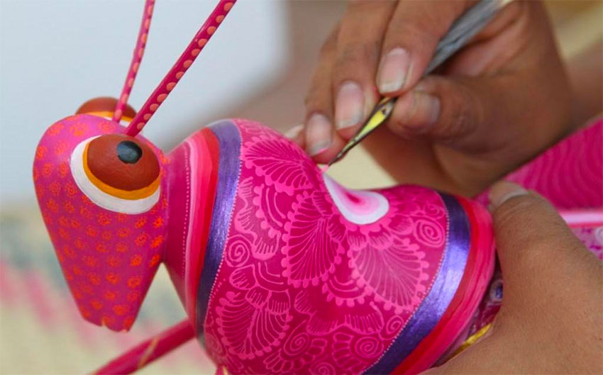 An artisan works on one of the pieces of whimsical folk art.