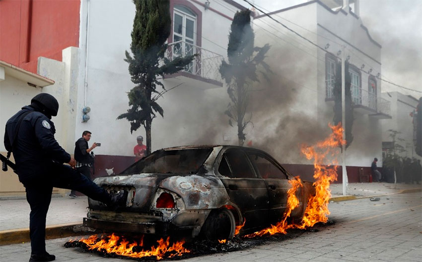 A vehicle burns during Thursday's protest in Amozoc.