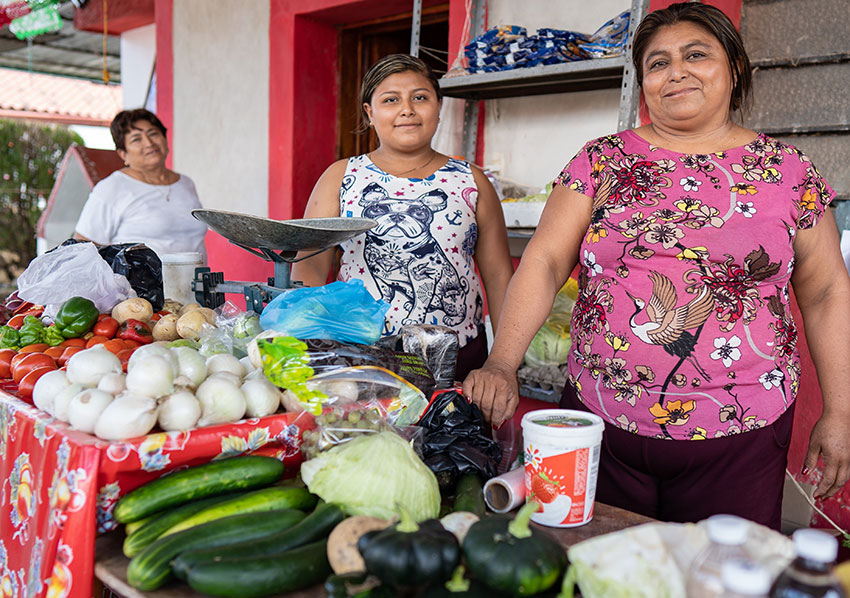 Flora, right, at her fruit and vegetable stand in Tenabo, Campeche.