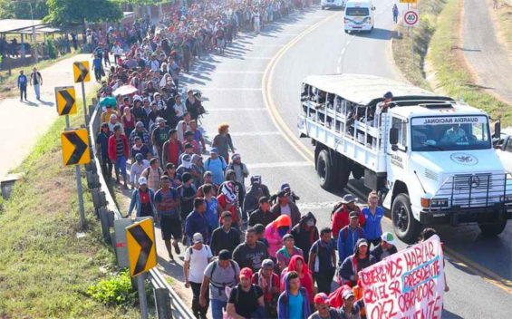 Migrants march north from the border Thursday morning.
