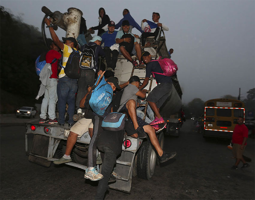 Migrants cling to a truck as they attempt to head into Mexico.