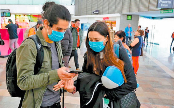 Travelers don masks for protection against coronavirus.