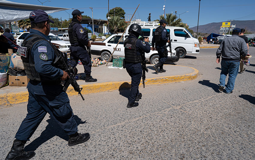 Federal Police officers guard the LeBaron family as they meet people in Chilapa, Guerrero.
