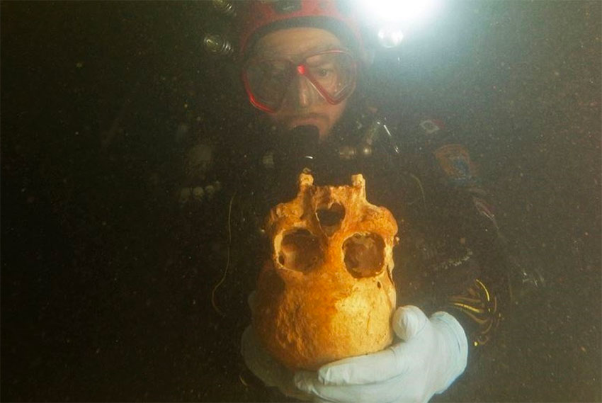 A diver with the skull of Chan Hol 3.