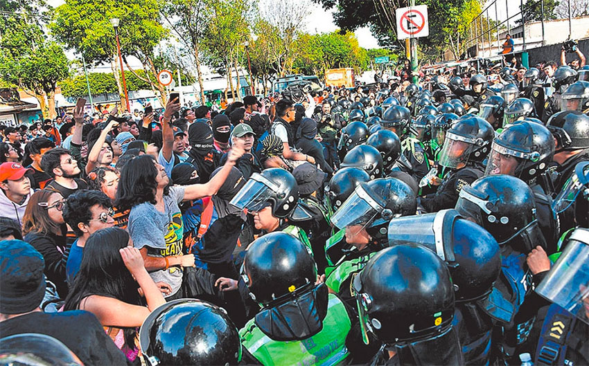 Police attempt to prevent masked protesters from entering the school, but were unsuccessful.