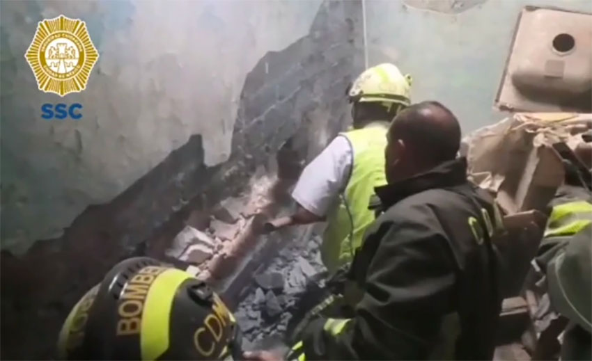 Rescue workers break through a wall to retrieve abandoned baby.