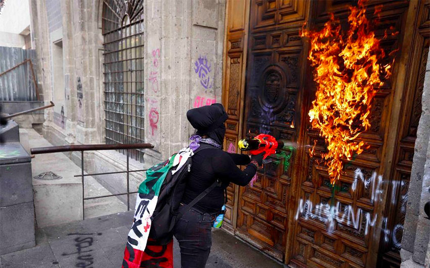 A protester sets fire to a door of the National Palace.