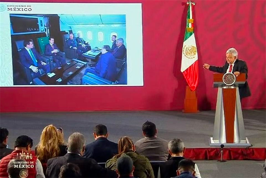The president displays a photo of Peña Nieto and his cabinet aboard the presidential plane.
