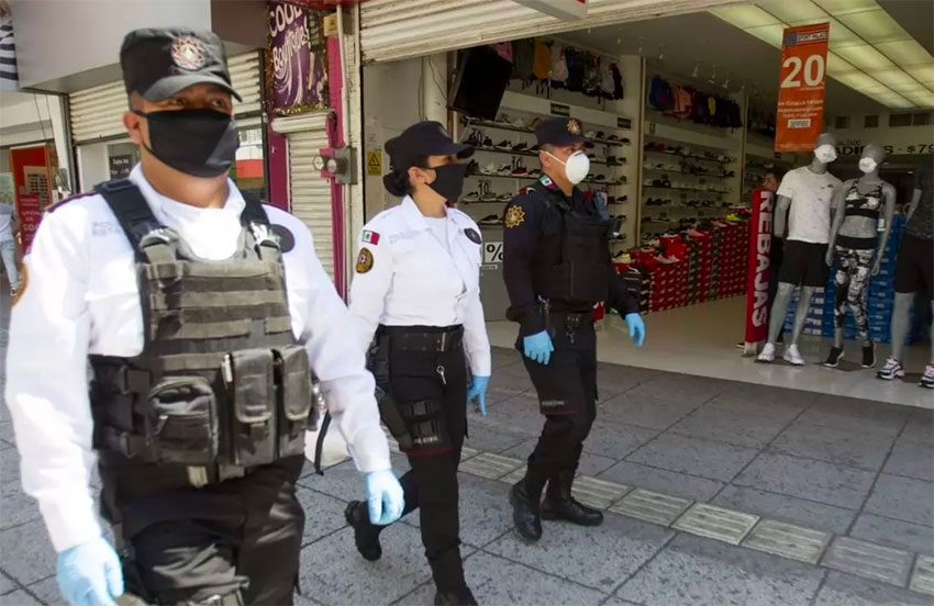 Masked security personnel on patrol in a shopping center.