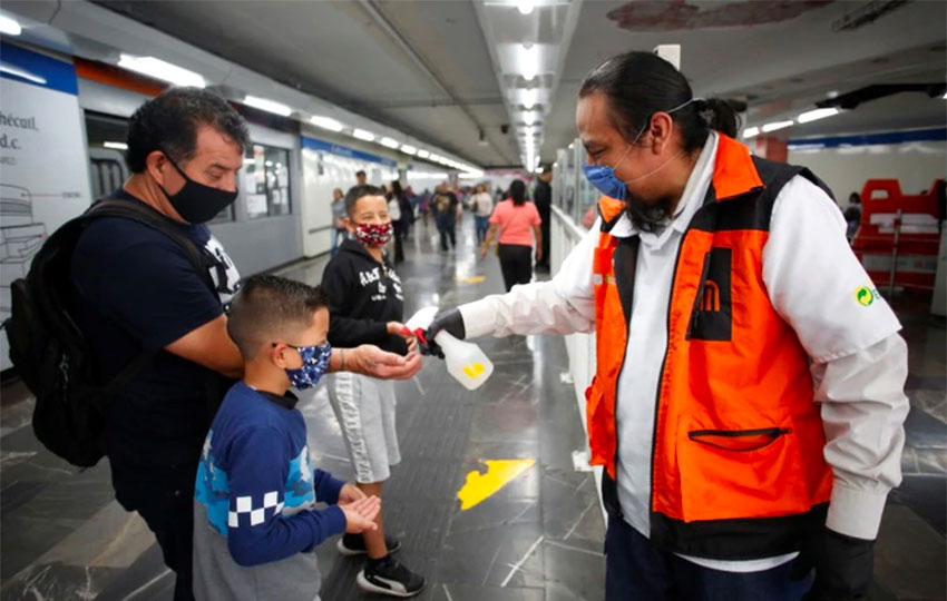 A Mexico City Metro worker dispenses hand sanitizer for passengers.