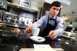 An Italian waiter practises 'social distancing.'