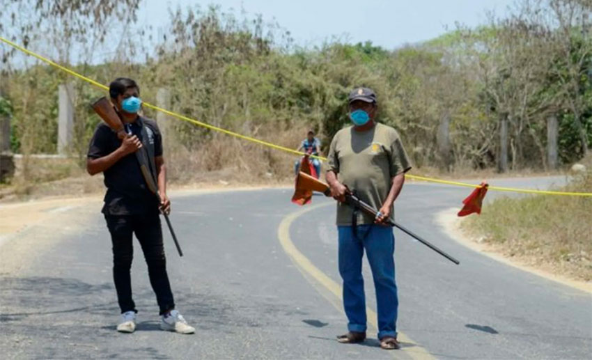 One of many checkpoints controlling access to communities across Mexico. The firearms would indicate they're serious.