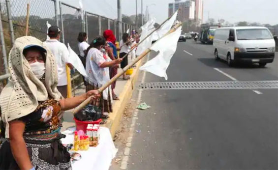 People line a highway in Guatemala on Saturday holding white flags to indicate they have no food. It may not be long before the flags appear in Mexico.