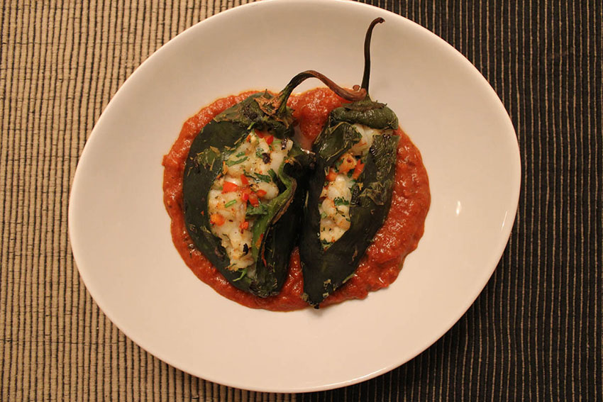 Stuffed poblano peppers with sauce.