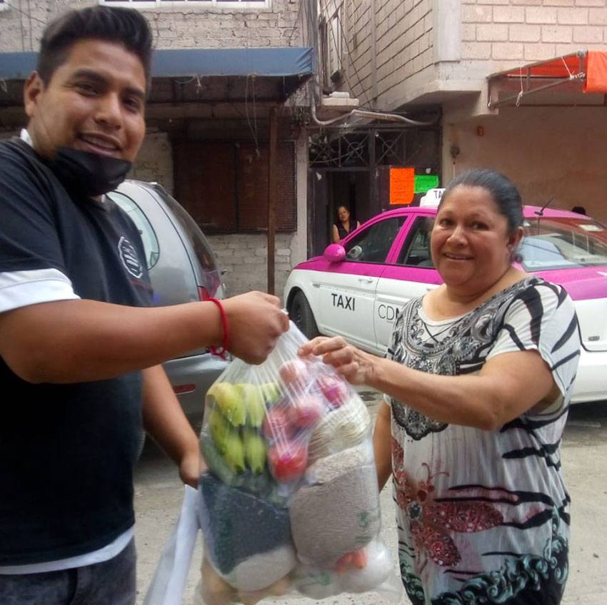 A volunteer, left, delivers a bag of supplies to a Mexico City resident.