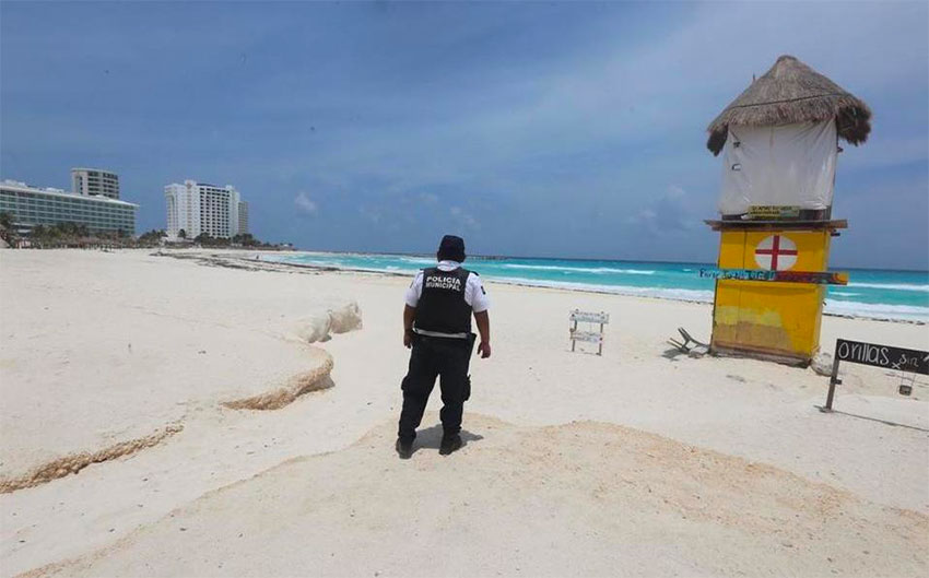 A police officer patrols an empty beach in Cancún