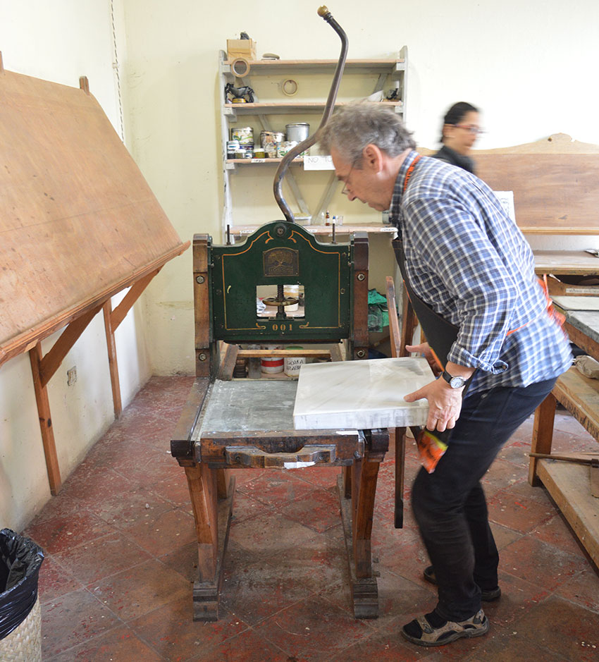 An artist places stone on a lithography press in one of La Ceiba's workshops