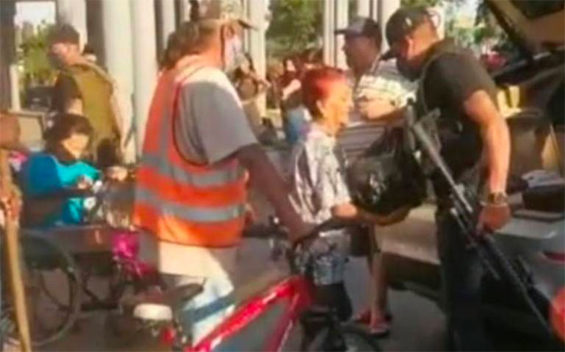 An armed man hands out provisions in Zapopan, Jalisco.