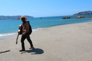 A lone musician seeks customers on a deserted Acapulco beach.