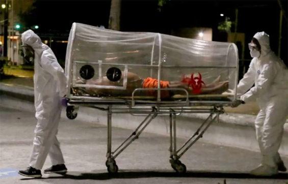 Paramedics move a Covid-19 patient.