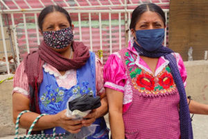 Women distribute face masks in Tlapazola, Oaxaca.