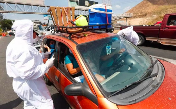 Health workers check the occupants of a vehicle heading out of Guadalajara on Friday.