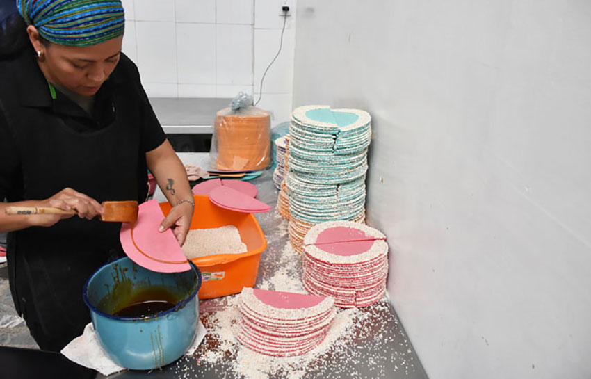 A woman makes amaranth wafers called obleas.