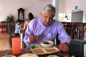 The president tucks into a meal of traditional food.