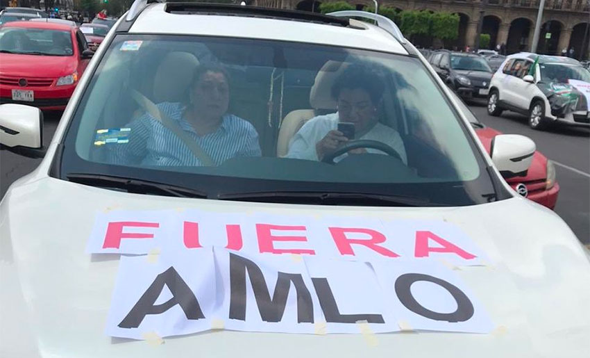 'AMLO out,' reads protesters' sign.