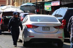 A traffic cop eyes a double-parked car in Oaxaca city.
