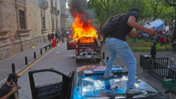 A protester vandalizes a police vehicle before it was set on fire Thursday in Guadalajara.