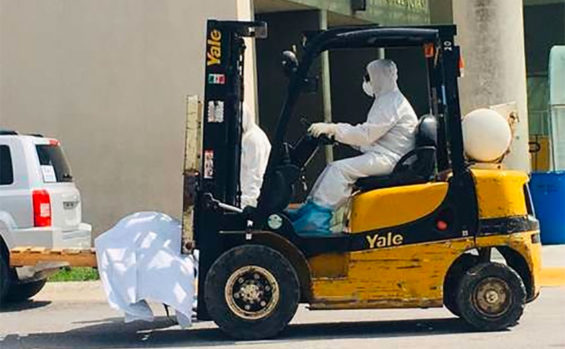 A forklift transports the body of a coronavirus victim
