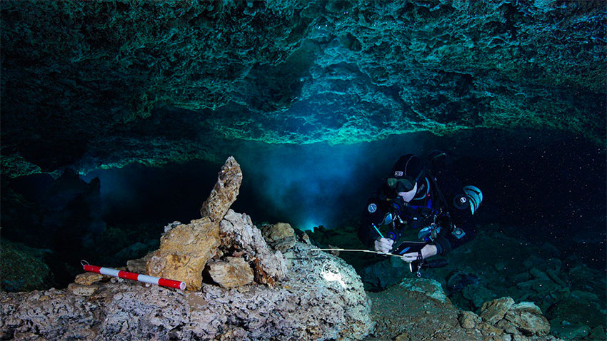 A diver examines a rock pile believed to be a navigational marker in the ocher mine.